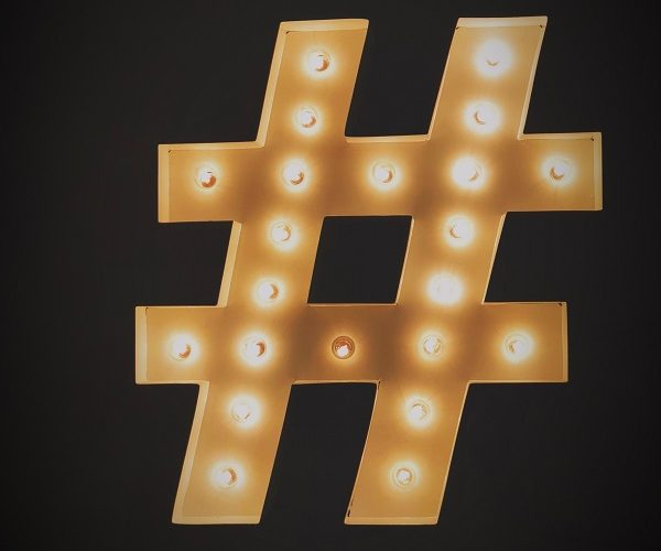 Gold hashtag light fitting on black background