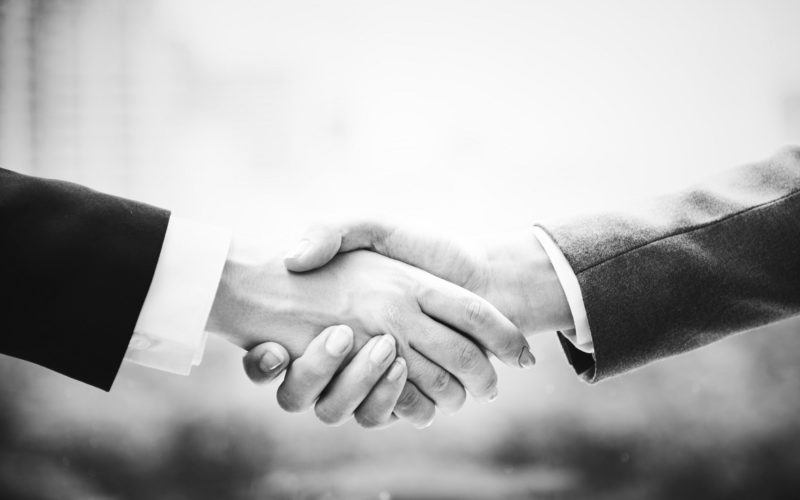 Greyscale image of two adults shaking hands